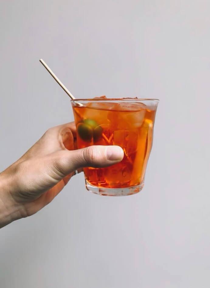 red cocktail drink held aloft.